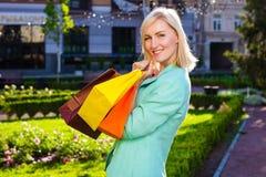 Πώληση, αγορές, τουρισμός και ευτυχής έννοια ανθρώπων - όμορφη γυναίκα με τις τσάντες αγορών στο ctiy Στοκ Φωτογραφία