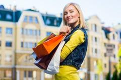 Πώληση, αγορές, τουρισμός και ευτυχής έννοια ανθρώπων - όμορφη γυναίκα με τις τσάντες αγορών στο ctiy Στοκ Φωτογραφίες