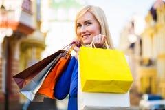 Πώληση, αγορές, τουρισμός και ευτυχής έννοια ανθρώπων - όμορφη γυναίκα με τις τσάντες αγορών στο ctiy Στοκ εικόνες με δικαίωμα ελεύθερης χρήσης