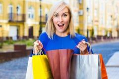 Πώληση, αγορές, τουρισμός και ευτυχής έννοια ανθρώπων - όμορφη γυναίκα με τις τσάντες αγορών στο ctiy Στοκ Εικόνες