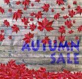 Πώληση φθινοπώρου και κόκκινα μειωμένα φύλλα που βάζουν στο ξύλινο υπόβαθρο Στοκ Φωτογραφίες