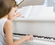 Πλάγια όψη λίγου παιδιού στο άσπρο πιάνο παιχνιδιού φορεμάτων Στοκ Εικόνες