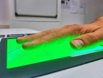 Πλάγια όψη από ένα άτομο που χρησιμοποιεί έναν ανιχνευτή δακτυλικών αποτυπωμάτων για τον προσδιορισμό Έννοιες βιομετρικής ή cyber Στοκ Φωτογραφίες