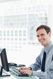 Πλάγια όψη ενός ευτυχούς εργαζομένου γραφείων που χρησιμοποιεί ένα όργανο ελέγχου Στοκ φωτογραφία με δικαίωμα ελεύθερης χρήσης