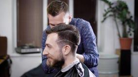 Πλάγια όψη ενός κεφαλιού της μοντέρνης συνεδρίασης ατόμων χαμόγελου γενειοφόρου στο barbershop που καλύπτεται με το μαύρο peignoi απόθεμα βίντεο