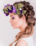 Πλάγια όψη ενός κοριτσιού με την κορώνα λουλουδιών που θέτει μέσα Στοκ Φωτογραφίες