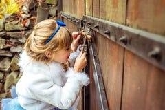 Πλάγια όψη ενός μικρού όμορφου κοριτσιού στο τοπίο της Alice στη χώρα των θαυμάτων που εξετάζει την κλειδαρότρυπα της πύλης Στοκ φωτογραφία με δικαίωμα ελεύθερης χρήσης