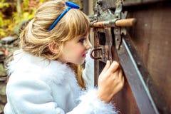 Πλάγια όψη ενός μικρού όμορφου κοριτσιού στο τοπίο της Alice στη χώρα των θαυμάτων που εξετάζει την κλειδαρότρυπα της πύλης Στοκ Φωτογραφία