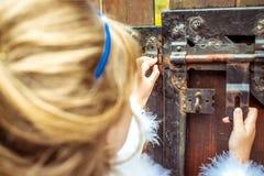 Πλάγια όψη ενός μικρού όμορφου κοριτσιού στο τοπίο της Alice στη χώρα των θαυμάτων που εξετάζει την κλειδαρότρυπα της πύλης Στοκ Φωτογραφίες