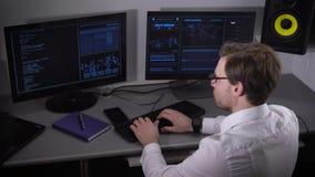 Πλάγια όψη ενός νέου freelancer που ντύνεται στο άσπρο πουκάμισο και με το smartwatch που λειτουργεί στο PC στο σπίτι Ανεξάρτητος φιλμ μικρού μήκους