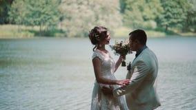 Πλάγια όψη ενός φιλώντας ζεύγους στη ημέρα γάμου τους Η ευτυχείς νύφη και ο νεόνυμφος γελούν σε μια όμορφη θέση σε μια όχθη ποταμ φιλμ μικρού μήκους