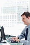 Πλάγια όψη ενός χαμογελώντας εργαζομένου γραφείων που χρησιμοποιεί ένα όργανο ελέγχου Στοκ Φωτογραφία