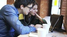Πλάγια όψη ενός χιλιετούς ζεύγους που χρησιμοποιεί τα ακουστικά μαζί σε έναν καφέ απόθεμα βίντεο