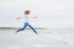Πλάγια όψη μιας περιστασιακής γυναίκας που πηδά στην παραλία Στοκ Φωτογραφίες
