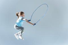 Πλάγια όψη της ευτυχούς humping άσκησης κοριτσιών με το πηδώντας σχοινί Στοκ Εικόνες