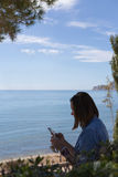 Πλάγια όψη της μαύρος-μαλλιαρής γυναίκας με το τηλέφωνο Στοκ Εικόνες