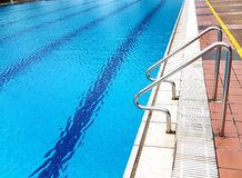 Πλάγια όψη της φωτεινής μπλε πισίνας με να προκαλέσει το κρύσταλλο - καθαρίστε το νερό και τα κιγκλιδώματα Στοκ εικόνα με δικαίωμα ελεύθερης χρήσης