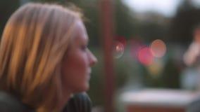 Πλάγια όψη της όμορφης σοβαρής νέας συνεδρίασης γυναικών σε έναν καφέ Κινηματογράφηση σε πρώτο πλάνο, θολωμένα φω'τα, αστική οδός απόθεμα βίντεο