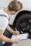 Πλάγια όψη του αυτοκινητικού μηχανικού γραψίματος στην περιοχή αποκομμάτων εξετάζοντας τη ρόδα του αυτοκινήτου στο εργαστήριο στοκ φωτογραφίες