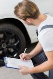 Πλάγια όψη του αυτοκινητικού μηχανικού γραψίματος στην περιοχή αποκομμάτων εξετάζοντας τη ρόδα του αυτοκινήτου στο εργαστήριο στοκ φωτογραφία με δικαίωμα ελεύθερης χρήσης