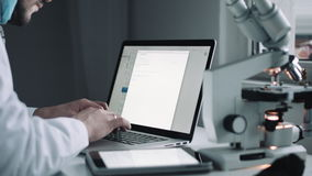 Πλάγια όψη του επιστήμονα που εργάζεται στο lap-top απόθεμα βίντεο