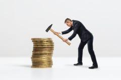 Πλάγια όψη του επιχειρηματία που συντρίβει το μεγάλο χρυσό σωρό νομισμάτων με το σφυρί, που απομονώνεται στο άσπρο υπόβαθρο Στοκ εικόνα με δικαίωμα ελεύθερης χρήσης