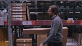 Πλάγια όψη του εργαζομένου με τον πόνο στην πλάτη ανυψωτικού το κιβώτιο στην αποθήκη εμπορευμάτων Σύγχρονα έπιπλα αποθεμάτων φιλμ μικρού μήκους