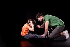 Πλάγια όψη του ελέγχοντας χρόνου ατόμων ενώ αγόρι που κάνει την άσκηση Τύπου Στοκ Εικόνες