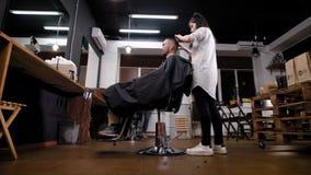 Πλάγια όψη του θηλυκού νέου κουρέα που στέκεται και που κάνει με τη χτένα και το ψαλίδι στο barbershop handsome man απόθεμα βίντεο
