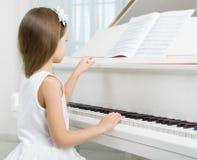 Πλάγια όψη του μικρού κοριτσιού στο άσπρο πιάνο παιχνιδιού φορεμάτων στοκ εικόνες