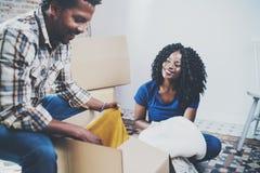Πλάγια όψη του νέου μαύρου αμερικανικού αφρικανικού ζεύγους με την κίνηση των κιβωτίων στο νέο διαμέρισμα Εύθυμη συνεδρίαση ζευγώ Στοκ Εικόνες