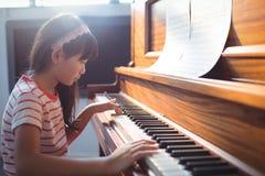 Πλάγια όψη του πιάνου άσκησης κοριτσιών στην τάξη Στοκ εικόνες με δικαίωμα ελεύθερης χρήσης