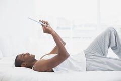 Πλάγια όψη του χαμογελώντας ατόμου Afro που χρησιμοποιεί την ψηφιακή ταμπλέτα στο κρεβάτι Στοκ Φωτογραφίες