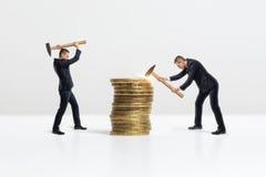 Πλάγια όψη των επιχειρηματιών που συντρίβουν το μεγάλο χρυσό σωρό νομισμάτων με το σφυρί, που απομονώνεται στο άσπρο υπόβαθρο Στοκ Φωτογραφίες