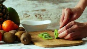 Πλάγια όψη των χεριών γυναικών που κόβει τα φρούτα ακτινίδιων με το μαχαίρι στον ξύλινο πίνακα, 4k φιλμ μικρού μήκους