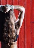 πλάτες γυναικών ικανότητας με το κόκκινο ξύλινο υπόβαθρο Στοκ φωτογραφία με δικαίωμα ελεύθερης χρήσης
