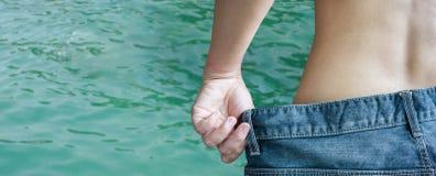 Πλάτη ή σπάνιος των τζιν τζιν γυναικών undress στη θάλασσα ή κρυστάλλινος Στοκ Φωτογραφία