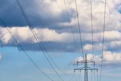Πλέγμα μετάδοσης υψηλής τάσης με το ζωηρό μπλε ουρανό Στοκ Εικόνες