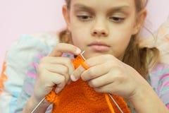 Πλέκει στις βελόνες το πορτοκαλί μαντίλι, εστιάζοντας στα spokes Στοκ Φωτογραφία