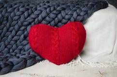Πλέξτε την κόκκινη καρδιά σε ένα πλεκτό κάλυμμα Στοκ Εικόνες