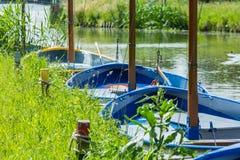Πλέοντας βάρκες που σχετίζονται ζωηρόχρωμες μέχρι μια όχθη ποταμού Στοκ φωτογραφία με δικαίωμα ελεύθερης χρήσης