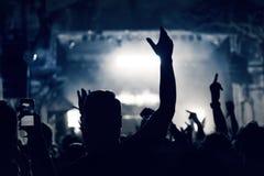 Πλήθος σε μια συναυλία μουσικής, ακροατήριο που αυξάνει τα χέρια επάνω, που τονίζονται στοκ φωτογραφία με δικαίωμα ελεύθερης χρήσης