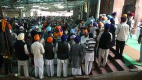 Πλήθος των ανθρώπων που μοιράζονται τα τρόφιμα στο Κα Langar, δημόσια κουζίνα γκουρού σε Amritsar απόθεμα βίντεο