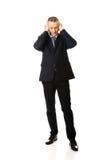 Πλήρες κουρασμένο μήκος άτομο που καλύπτει τα αυτιά με τα χέρια Στοκ Φωτογραφία