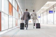 Πλήρες μήκος οπισθοσκόπο των επιχειρηματιών με τις αποσκευές που τρέχουν στην πλατφόρμα σιδηροδρόμου Στοκ Εικόνες