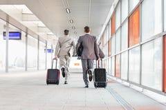 Πλήρες μήκος οπισθοσκόπο των επιχειρηματιών με τις αποσκευές που τρέχουν στην πλατφόρμα σιδηροδρόμου Στοκ εικόνες με δικαίωμα ελεύθερης χρήσης