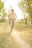 Πλήρες μήκος της μουσικής ακούσματος ατόμων τρέχοντας στο πάρκο Στοκ Φωτογραφίες