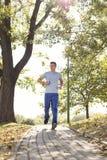Πλήρες μήκος της μουσικής ακούσματος ατόμων jogging στην πορεία στο πάρκο Στοκ εικόνες με δικαίωμα ελεύθερης χρήσης