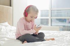 Πλήρες μήκος της μουσικής ακούσματος κοριτσιών στα ακουστικά στην κρεβατοκάμαρα Στοκ εικόνες με δικαίωμα ελεύθερης χρήσης