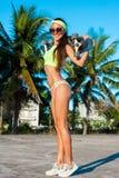 Πλήρες μήκος της νέας μοντέρνης γυναίκας στα γυαλιά που στέκονται με skateboard και που κοιτάζουν στη κάμερα Στοκ Εικόνα
